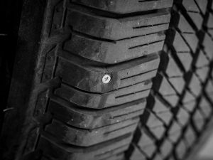 Nail stuck in a tyre, giving the tyre a puncture.
