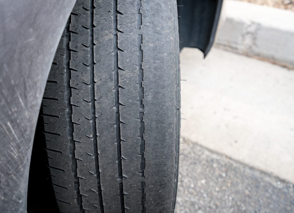 Close up of a tyre that has little tread left and beginning to bald. A sign that your car needs new tyres.